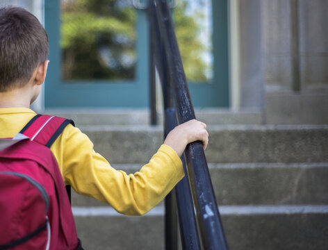 Boy in red backpack holds railing as he walks up the school steps