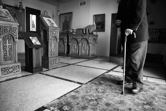 Lower portion of old man walking with cane at Greek church