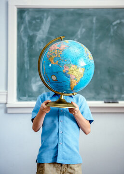 Child standing in classroom holds a globe up in front of his face
