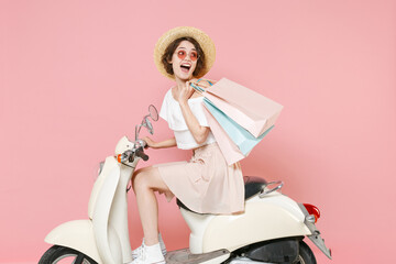 Side view of excited young woman 20s wearing white summer clothes hat glasses hold package bag with...