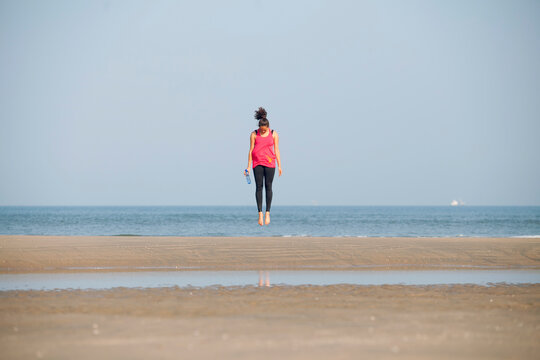 Healthy young woman jumping on the beach during her workout.