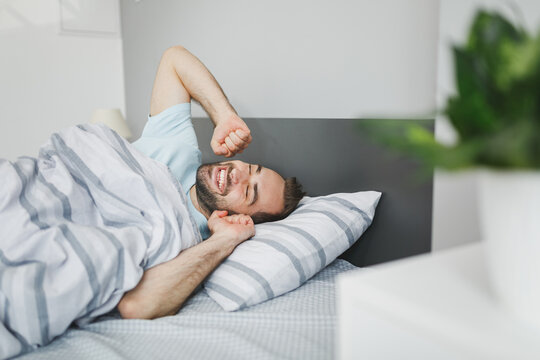 Smiling attractive young bearded man wearing basic blue t-shirt sleeping waking up stretching hands lying in bed with striped sheet pillow blanket resting relaxing spending time in bedroom at home.