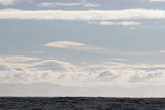 Skyscape with waving clouds above the coastline