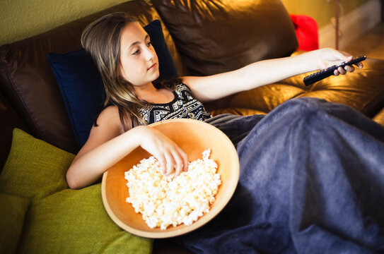Young girl watching the TV and holding the remote