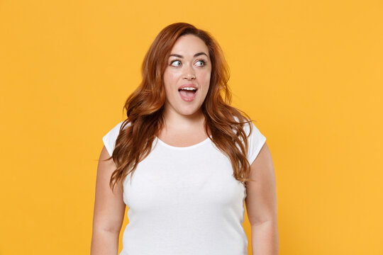 Excited young redhead plus size body positive female woman girl 20s in white blank design casual t-shirt posing keeping mouth open looking aside isolated on yellow color background studio portrait.