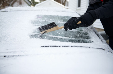 Man uses scraper to remove the snow and ice from the windshield of his car