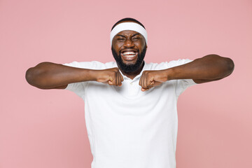 Cheerful young bearded african american fitness sports man 20s in white headband t-shirt doing stretching exercising spending time in gym isolated on pastel pink color wall background studio portrait.