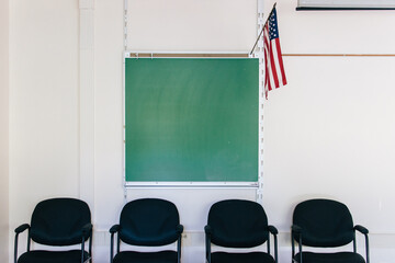 classroom with blackboard, chairs, and American flag