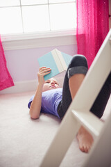 Girl: Young Girl Reads Book in Bedroom