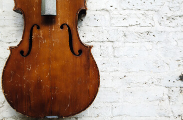 Old weathered cello against a textured white wall