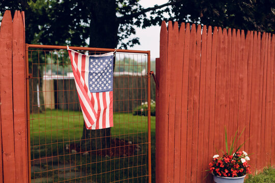 An Amerian flag hangs on an old gate between a red fence.