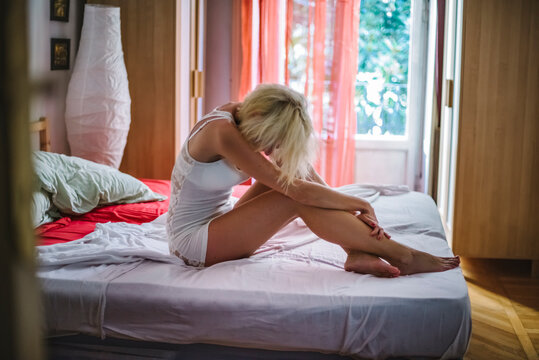 Worried woman sitting on the bed