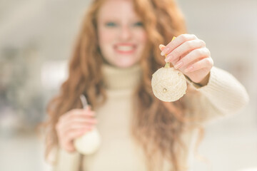 Smiling Woman Holding Christmas Ornaments