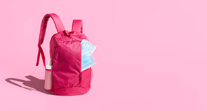 Back to school in pandemic concept. School backpack with face mask and sanitizer