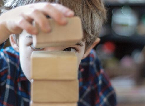 Boy stacks blocks with careful precision