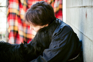 Woman sits down hugging, cuddling and holding in her arms a giant Schnauzer dog