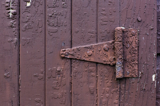 A rusty hinge on the side of a brown, wooden barn.
