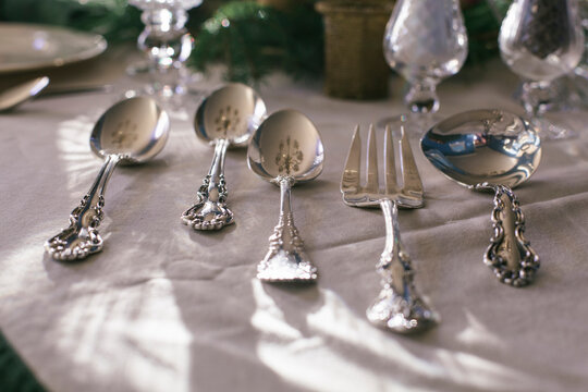 Silver serving utensils on a tablecloth at Thanksgiving.
