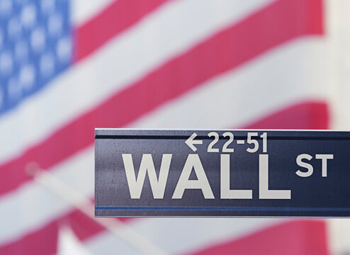 Wall Street sign with USA flag on background.