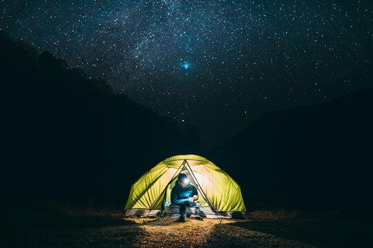ソロキャンプ 星空と山でテント泊する男性