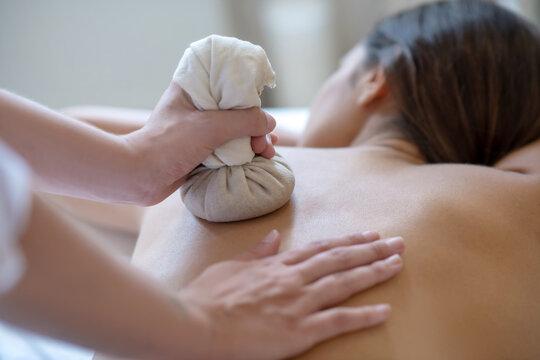Young dark-haired woman having bags ayurvedic massage
