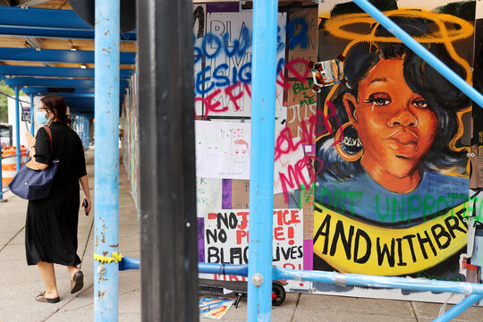A woman walks near a wall of protest signs, including a portrait of Breonna Taylor at Black Lives Matter Plaza in Washington