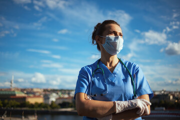 confident modern physician woman outdoors in city against sky