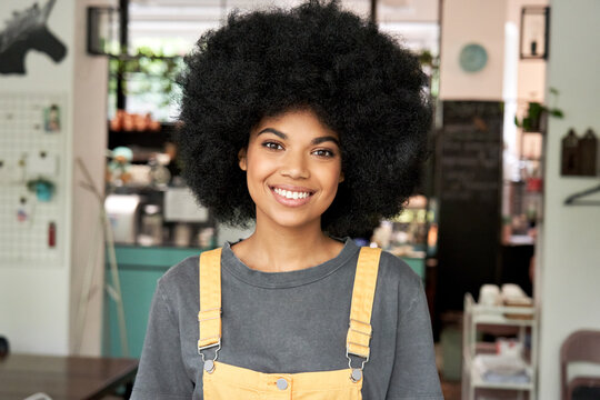 Happy stylish African American gen z hipster female student with Afro hair looks at camera stands in cozy cafe interior. Smiling mixed race young woman wears yellow sundress headshot portrait.