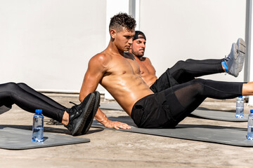 Group of athletic men doing abs workout outdoors on the floor, no equipment home exercise in the open air concept
