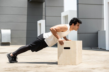 Handsome Indian sports man doing push up exercise outdoors on building rooftop, home workout in the open air concept