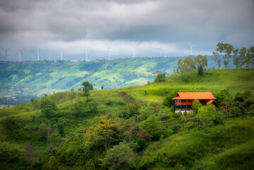 Landscape natural view that can see orange house, trees and can see many wind turbines as background at Phetchabun in Thailand.