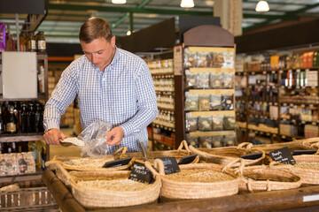 Man choosing bulk products in supermarket