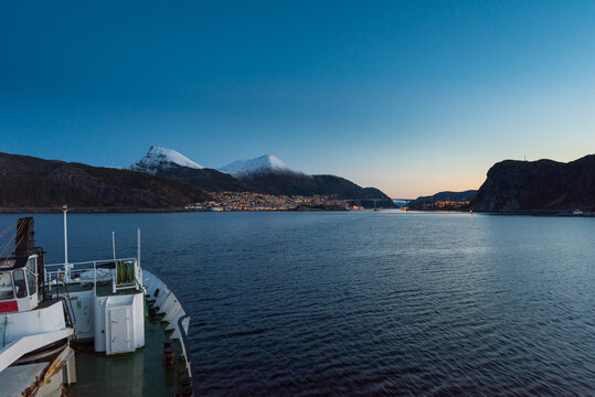 Arriving in Maloy, Norway with cruise ship in early morning with snow capped mountains on clear winter day