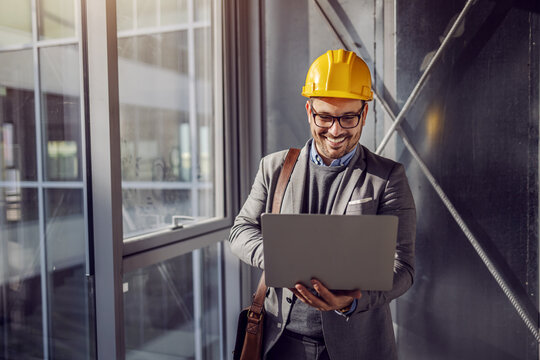 Young smiling architect standing near window in building in construction process and looking at blueprints on laptop.
