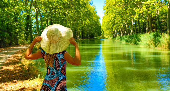 woman with dress and hat enjoying France landscape- Canal du Midi