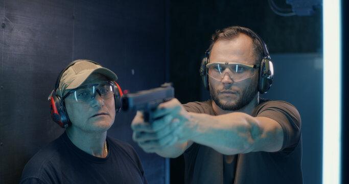 Mature instructor teaching man to shoot pistol