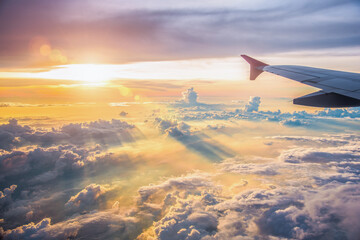 Beautiful sunset sky above clouds with dramatic light. Cabin view from airplane window. - image