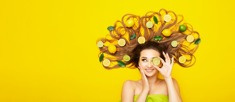 beautiful girl on yellow background with citrus style on long hair,young woman cover eye with lemon slice, cheerful mood