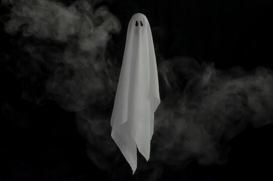 White ghost sheet flying in dark background with smoke. Halloween scary concept.