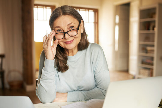 Mature age, people and distant work concept. Attractive confident middle aged woman in glasses working from home, sitting in front of open laptop, doing paperwork, looking at camera with happy smile