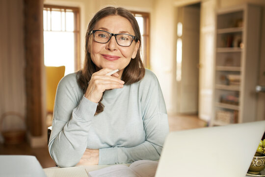 Portrait of gray haired mature businesswoman in eyewear using portable computer for remote work, studying documentation. Attractive retired female teacher holding pen, checking home assignment
