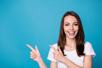 Photo of attractive pretty funny charming lady good mood directing fingers side empty space showing...