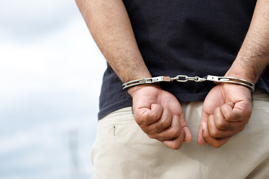 Arrest the offender. Prison male criminal standing in handcuffs with hands behind back.