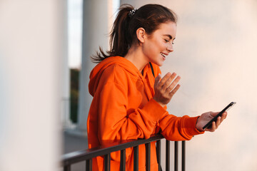 Image of woman making video call on cellphone while bending over railing
