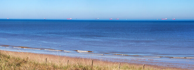 Wassenaar, Netherlands: sunny clear day at the beach; on the horizon eight freighters waiting to enter Rotterdam harbour
