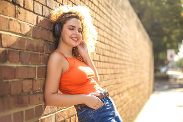 Curly hair girl chilling in the street, lying on a brick wall and listening music with her headphones