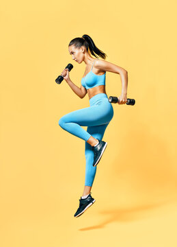 Sporty woman in sportswear jumping with dumbbells on yellow background