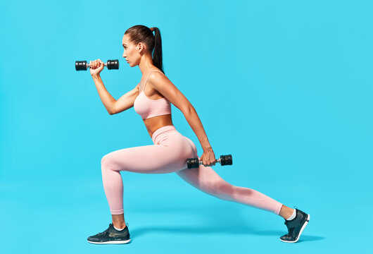 Sporty woman doing lunges exercises with dumbbells
