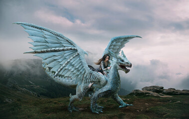 A young woman sits astride a dragon. Fantasy photography. A huge creature with spikes and wings stands on top of a mountain. Beautiful nature sky and white clouds.