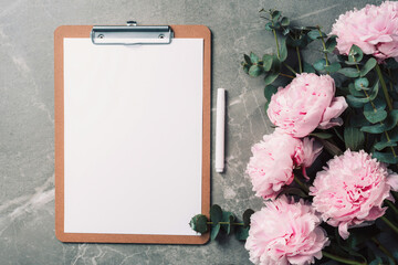 Fashion feminine blogger concept. Feminine workspace with notebook, clipboard, paper, pink peony, eucalyptus flower on marble background. Blogger, feminine business concept. Flat lay. Mock up